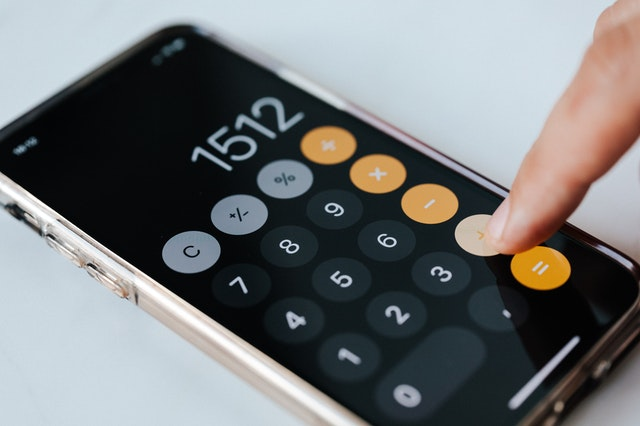 A person on a calculator to denote someone calculating their budgeting based on CERB ends and being replaced by new EI, CRB, CRSB and CRCB programs.